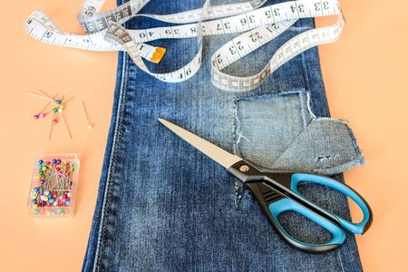 Blue jeans with large hole folded in half, sewing pins in a box, white tailor tape with centimeters and inches and scissors. Shorten the jeans. DIY shorts out of jeans. Top view.