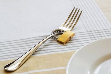 Metal fork locked with padlock near white empty plate on a tablecloth. Control the amount of food eaten, losing weight and dieting consepts. Conscious food intake. 写真素材