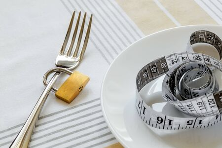 Metal fork locked with padlock and white plate with measuring tape on a tablecloth. Control the amount of food eaten, losing weight and dieting consepts. Conscious food intake.