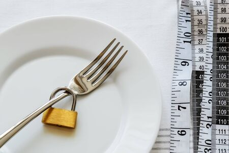 Metal fork locked with padlock on a white plate and measuring tape near it.  Control the amount of food eaten, losing weight and dieting consepts. Conscious food intake. Top view.