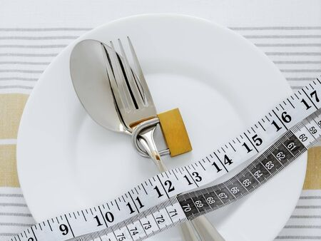 Metal fork locked with padlock and measuring tape are on a white plate. Control the amount of food eaten, losing weight and dieting consepts. Conscious food intake. Top view. Archivio Fotografico