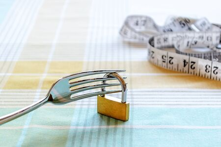 Metal fork locked with padlock and measuring tape over tablecloth. Control the amount of food eaten, losing weight and dieting consepts. Conscious food intake. Front view.