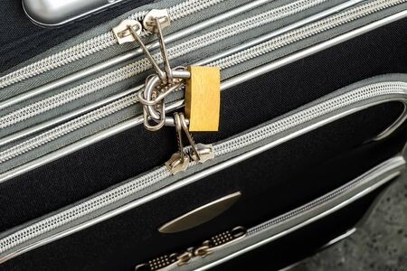 Zippers locked with a padlock on a black travel suitcase. Protect the baggage from theft during the trip. Luggage theft prevention. Security of the suitcase in travel. Top view.