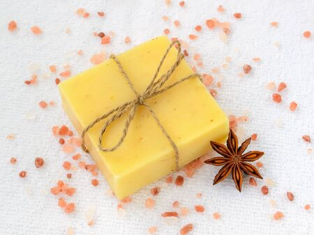 Yellow handmade soap bar and crystals of pink himalayan salt over a white terry cotton towel. Natural toiletries and hygiene products with herbs and essential oils. Top view. 版權商用圖片