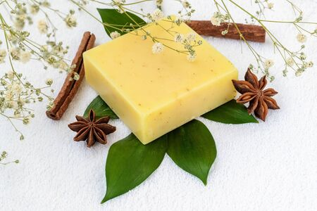 Yellow handmade soap bar on a green leaves over a white terry cotton towel. Natural toiletries and hygiene products with herbs and essential oils. Top view. Stock Photo
