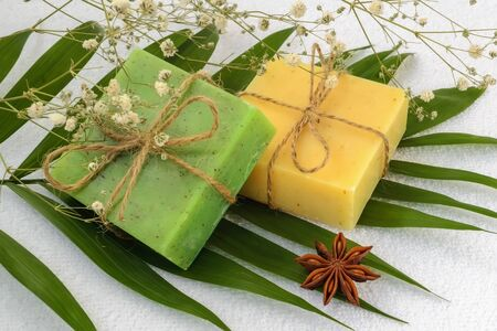Green and yellow handmade soap bars on a green leaves over a white terry cotton towel. Natural toiletries and hygiene products with herbs and essential oils. Top view.