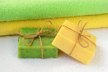 Green and yellow handmade soap bars near the same colors terry towels over a white one. Natural toiletries and hygiene products with herbs and essential oils. Front view.