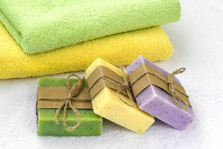Green, yellow and purple handmade soap bars near yellow and green terry towels over a white one. Natural toiletries and hygiene products with herbs and essential oils. Front view. Stock Photo