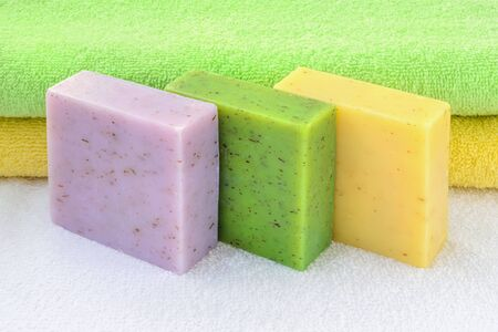 Purple, green and yellow handmade soap bars near yellow and green terry towels over a white one. Natural toiletries and hygiene products with herbs and essential oils. Front view.