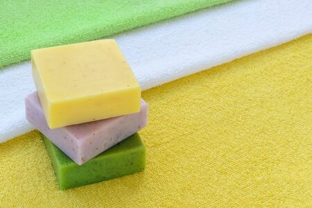 Stack of green, purple and yellow handmade soap bars on a yellow, white and green terry towels. Natural toiletries and hygiene products with herbs and essential oils. Copy space.