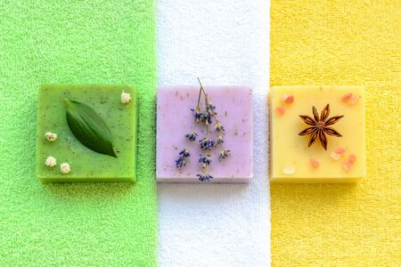Green herb soap, purple lavender one and one more yellow with herbs and himalayan salt on  a green, white and yellow terry towels. Natural toiletries and hygiene products with herbs and essential oils. Flat lay.