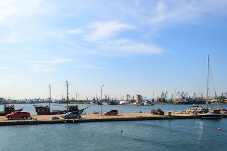 View of the water area of the small seaport with yachts, cargo ships and cranes on a clear and calm sunny day. Industrial sea scape.