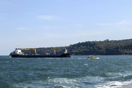 Small yellow pilot ship leads a large black cargo container ship to the seaport on a sunny day during small storm. Industrial seascape. On a day. Stok Fotoğraf