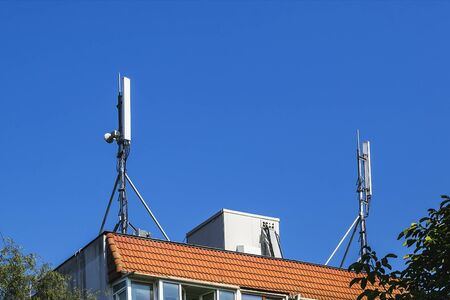 Two antennas of cellular communication on an orange tiled roof of a multi-storey residential building against blue sky. Low angle view. 版權商用圖片