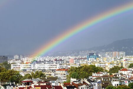 Close-up of gorgeous rainbow over residential area of the city. Scenic summer cityscape with a rainbow. Beauty in nature. Banco de Imagens