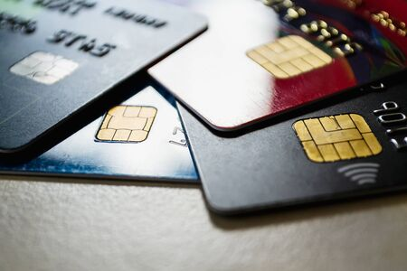 Few plastic credit cards with chips and contactless pay technology close-up. Low key shot with old credit cards. On a table.
