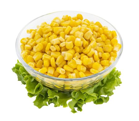 Canned sweet corn in a glass bowl. Side dish and ingredient for salads. Isolated on a white background. Vegetarian food.