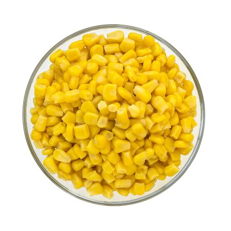 Top view of canned sweet corn in a glass bowl. Side dish and ingredient for salads. Isolated on a white background. Vegetarian food.