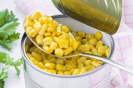 Spoon of canned sweet corn over a freshly opened tin can on a table. Side dish and ingredient for salads. Vegetarian food. Stok Fotoğraf