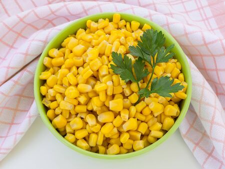 Canned sweet corn in a green bowl near checkered kitchen towel on a table. Side dish and ingredient for salads. Vegetarian food. Top view. Stok Fotoğraf