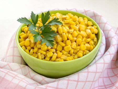 Close-up of canned sweet corn in a green bowl near checkered kitchen towel. Garnish and ingredient for salads. Vegetarian food. Side view. Stok Fotoğraf
