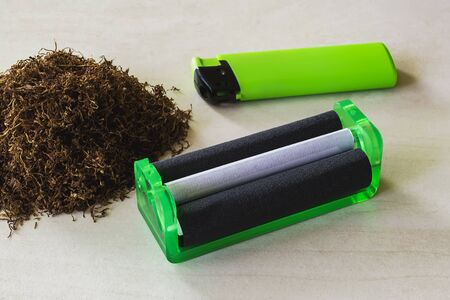 Green cigarette rolling machine, green lighter and pile of tobacco on a white table. Making cigarettes with pipe tobacco at home. Front view. Stockfoto