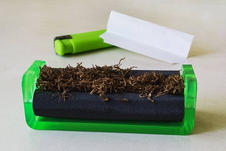 Green cigarette rolling machine with tobacco, cigarette paper and green lighter on a white table. Making cigarettes with pipe tobacco at home. Front view. Stockfoto