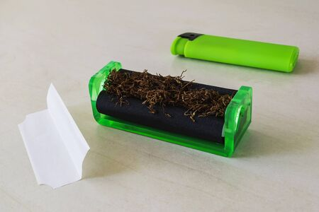 Green cigarette rolling machine with tobacco, green lighter and cigarette paper on a white table. Making cigarettes with pipe tobacco at home. Front view.