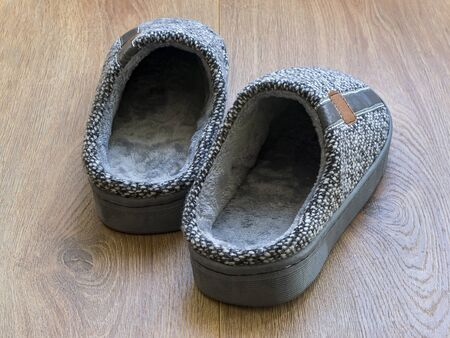 Pair of a gray mens house slippers on a brown wooden floor. Cozy, warm and comfortable domestic shoes. Back view.