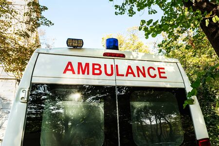 Stationary white ambulance car with a blue warning light on a roof. An emergency medical service van. On a sunny autumn day. Rear view.