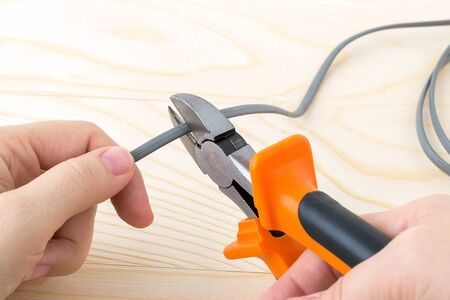 Woman hand holdins a metall side cutters with orange black rubber handles and cutting a wire over a rough wooden background. Electrician tool for repair and construction. Front view.