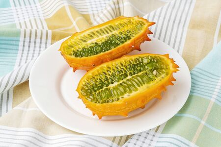Two halves of fresh orange kiwano (cucumis metuliferus, horned melon) on a white plate over a table. Fruits, vegetables, vegetarian and healthy eating. Front view.