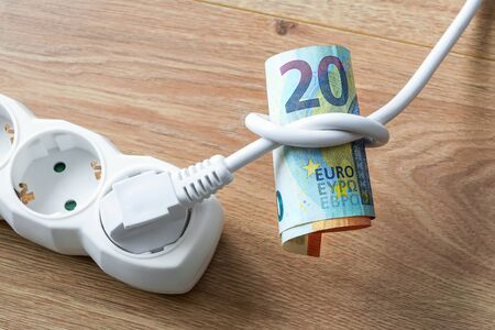 White electric cable with plug tied to a knot on a roll of euro banknotes. Cost of electricity and expensive energy concepts. On a wood surface. Top view.