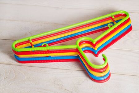 Five multicolored plastic clothes hangers on a light wooden surface. Set of new colorful plastic clothes hangers. Household items. Domestic life. Top view.