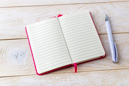 Opened lined paper notebook in a pink cover and white ballpoint pen on a white wood textured surface. Business, education and keep a diary concept. Copy space.
