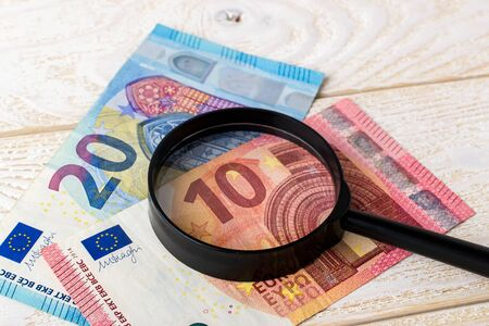 Magnifier on euro banknotes over a white wooden surface. Check the authenticity of money. Wealth, poverty and counterfeiting money concept. Front view.