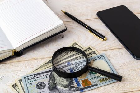 Magnifier on dollar banknotes near pen, note book and smartphone on a white wooden surface. Check the authenticity of money and business concept. Top view.