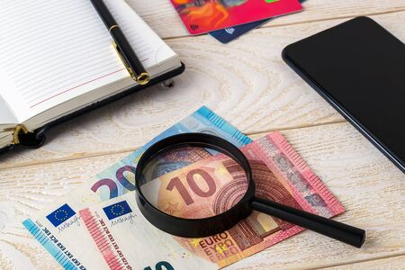 Magnifier on euro banknotes near pen, note book, credit cards and smartphone on a white wooden surface. Check the authenticity of money and business concept. Top view.