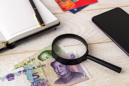 Magnifier on chinese yuan near pen, note book, credit cards and smartphone on a white wooden surface. Check the authenticity of money and business concept. Top view. Stock fotó