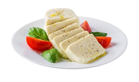 Plate with rectangular slices of mozzarella cheese, fresh basil and quarters of tomato isolated on white background. Healhy mediterranean cuisine and vegetarian food. Front view. Banco de Imagens