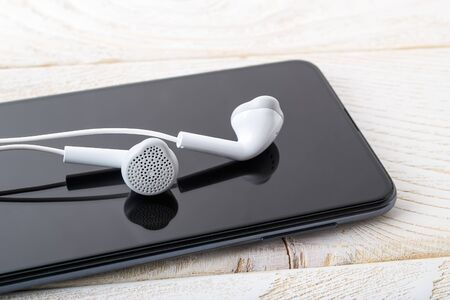 White earphones reflects in a black smartphone screen on a white wooden table. Listen to music. Modern personal device with touchscreen for music and communication. Top view.