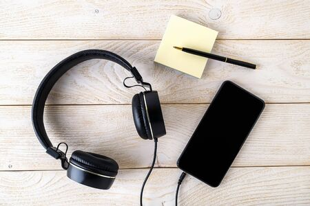 Smartphone, black headphones and pen with sticky notes block on a white wooden table. Modern personal device with touchscreen for music and communication. Top view.