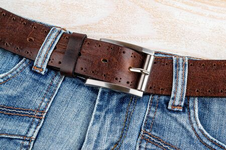 Jeans with brown genuine leather belt with classic metal buckle on a wooden background. Men's stylish leather accessories. Top view.