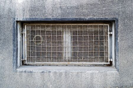 Rectangular basement or cellar window is tightened with wire metal mesh and grille. Technical floor window in the wall of an old gray building. Front view.