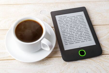 Copy space on a screen of e-book reader near cup of hot coffee on a white wooden table. E-reading for pleasure and education. Front view. Stock Photo