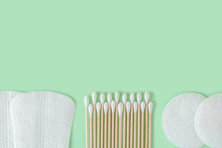 Cotton pads, cotton buds wood stick and few disposable panty liners on a pastel mint background. Flat lay of feminine hygiene items. Copy space. Top view.