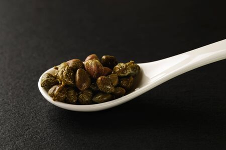 Pickled capers in a white chinese porcelain spoon on a black stone serving board. Sauces and seasonings for meat, fish and vegetables. Front view.