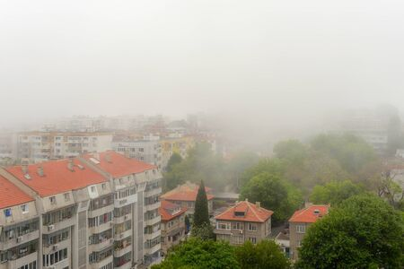 Residential lowrise houses and streets with green trees in dense fog at summer day. Thick fog came from the sea and covered the city. Climate and weather changes. High angle view.