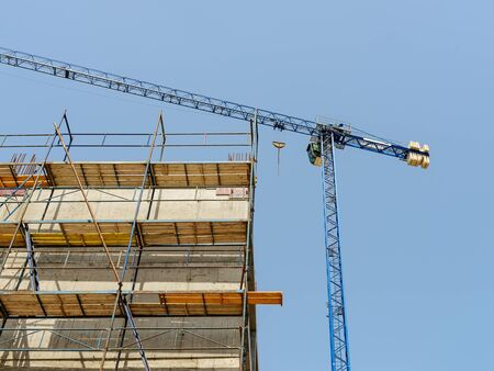 Blue tower crane with cargo near a wall of concrete building under construction on a sunny day. Modern construction machinery against blue sky. Scaffolds on the wall. Low angle view.