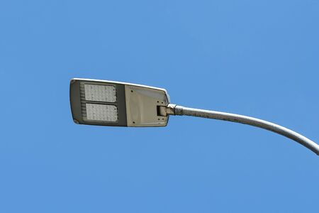 Led streetlight against clear blue sky background. Modern energy-saving technologies for lighting streets and roads. Led street lamp. Low angle view. Фото со стока
